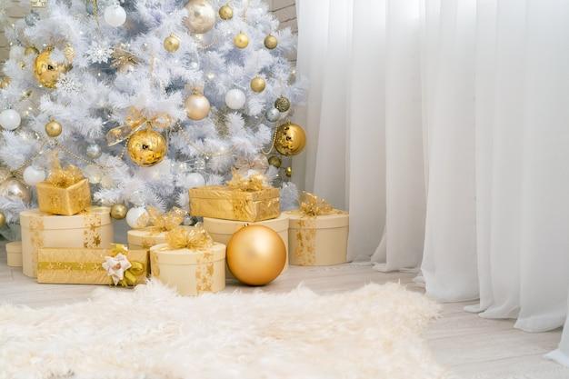 Рождественские подарки лежат под белым деревом, украшенным золотыми шарами.