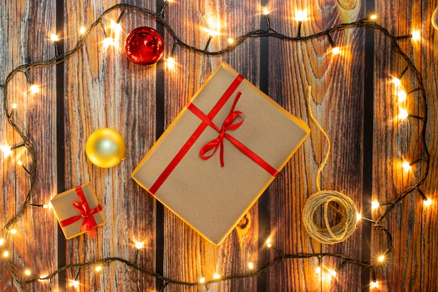 Christmas gifts and lights on wooden floor