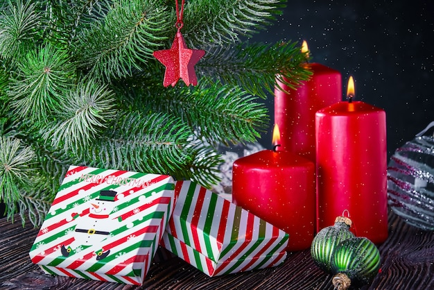Christmas gifts, lit candles and decorated with a spruce branch. new year's background with free space for text.