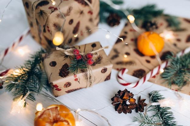クリスマスプレゼント、ロリポップ、白い木製のテーブルにタンジェリン。
