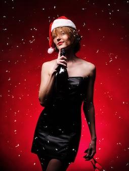 크리스마스 선물. 산타 모자에 모델 소녀입니다. 샴페인과 안경, 절연을 들고 소녀