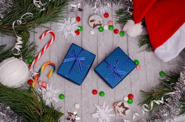 クリスマスのおもちゃ、針葉樹の枝、サンタ帽子、お菓子と灰色のテーブルの上のクリスマスプレゼント