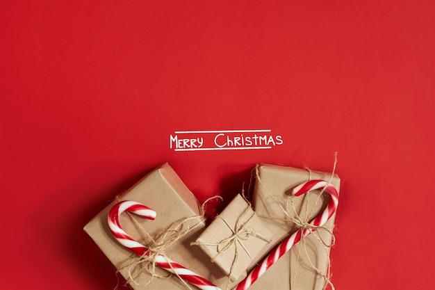 真っ赤な背景にクリスマスプレゼント。クリスマスと新年のテーマ。あなたのテキスト、願い、ロゴのための場所。モックアップ。上面図。スペースをコピーします。静物。フラットレイ。
