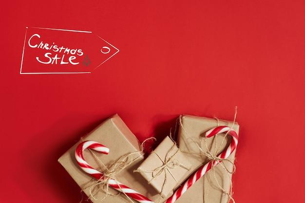 真っ赤な背景にクリスマスプレゼント。クリスマスと新年のテーマ。あなたのテキスト、願い、ロゴのための場所。モックアップ。