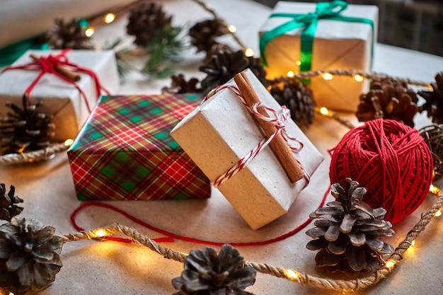 コーンとモミの枝の花輪が付いた赤いウールの市松模様の格子縞の背景にクリスマスプレゼント