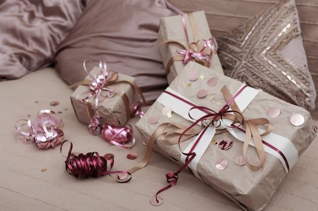 枕の間のベッドの上のクリスマスプレゼント、クリスマスプレゼントのラッピングコンセプト。