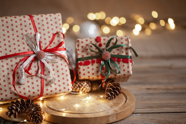 Christmas gifts packed in craft paper with ribbons, garland and decorative cones on blurred background.