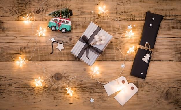 Рождественские подарки упакованы в черную и полосатую бумагу и украшены звездами и гирляндой на столе.
