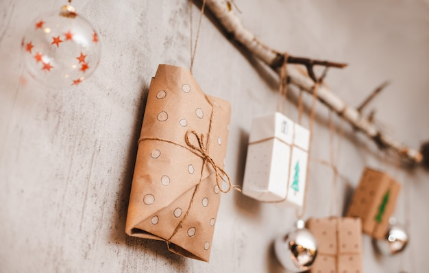Christmas gifts packed with kraft paper and hand made decorations hang on a rope tied to a stick against a gray concrete wall.