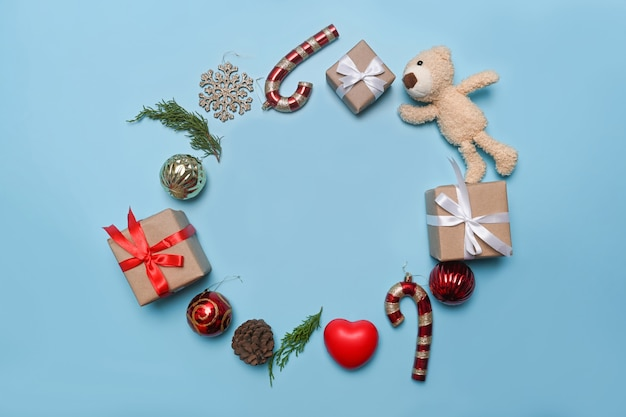 파란색 배경에 크리스마스 선물, 소나무 콘, 전나무 나뭇가지.