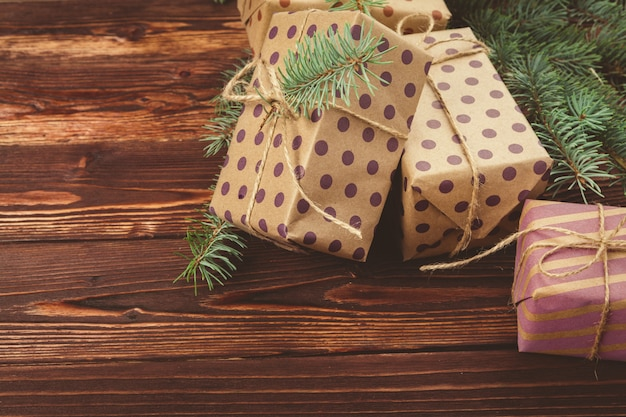 Christmas gifts and pine tree branches on wooden table, top view