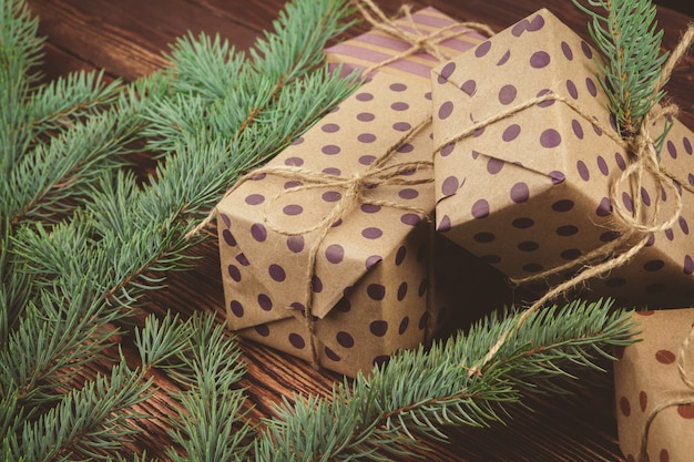 Christmas gifts and pine tree branches on wooden table