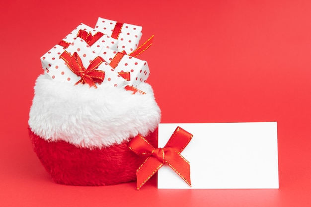 Christmas gifts in santa claus sack wrapped in gift paper polka on red background with note mock up.