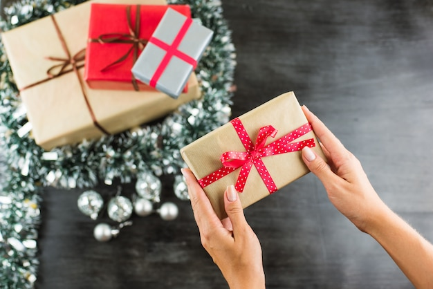 Christmas gifts on a table with black and hands holding present