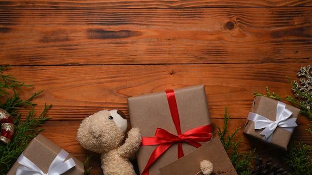 クリスマスプレゼント、テディベア、木製の背景のモミの木の枝にホットコーヒーのカップ。