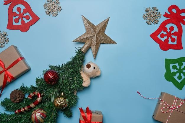 파란색 배경에 크리스마스 선물, 테디 베어, 전나무 나뭇가지. 크리스마스와 새 해 개념입니다.