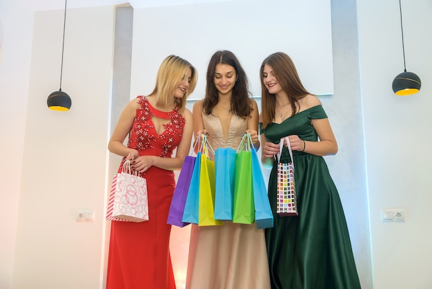 Christmas gifts, three young ladies with present bags posing in elegant dress