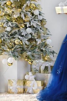 装飾されたクリスマスツリーの背景の下にクリスマスプレゼントエレガントな青いドレスの一部
