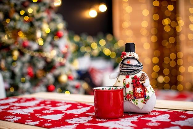 Рождественские подарки под елкой. снеговик держит елку. новый год уютный фон. свободное место для текста