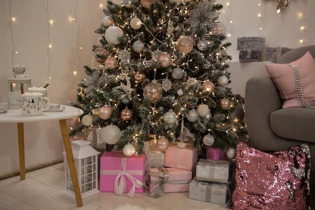 お祝いのクリスマスツリーの下のクリスマスプレゼント、新年のお祝い、リビングルームのインテリア、ソフトフォーカス