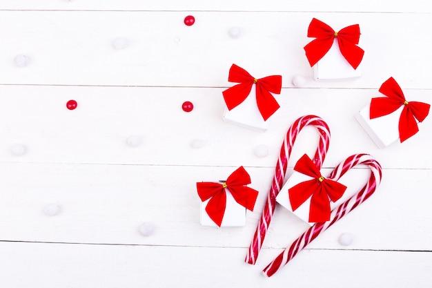 クリスマスプレゼント、白い木製の背景に赤い弓とキャンディーと白い小さな箱