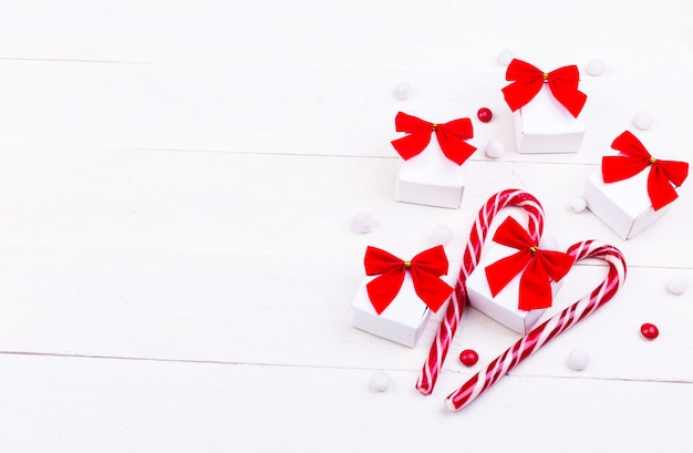 Christmas gifts, white little boxes with red bow and candies on white wooden background.