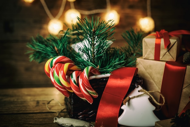 Christmas gifts with boxes, coniferous, basket, candy cane cones on wooden background