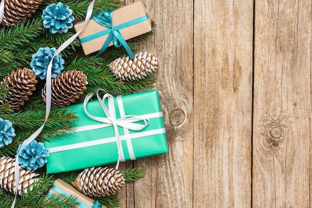 板のテーブルにモミの枝が付いたクリスマスプレゼント。