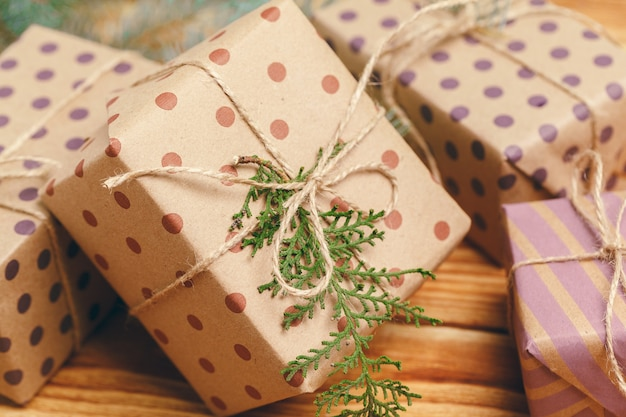 Christmas gifts with fir tree branches on wooden background