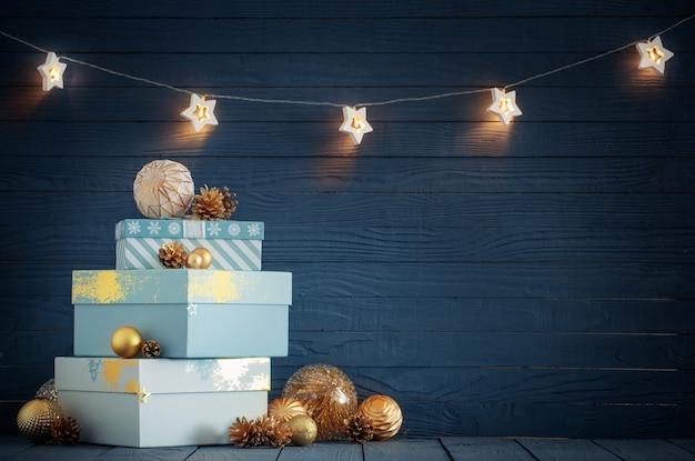 青い木製の背景に金色の装飾が施されたクリスマスプレゼント