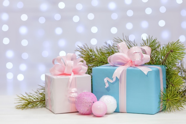 Christmas gifts with large bows wrapped in pink and naked paper