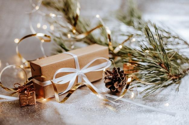 Рождественские подарки с шишками и еловыми ветками в новогодней атмосфере