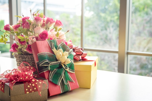 Christmas gifts with rose vase and santa hat on wooden table interior of room view through window