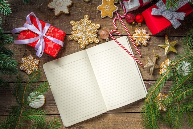 Christmas gifts with tree branches and gingerbread cookies next to empty notebook