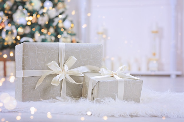 Christmas gifts with white ribbon under christmas tree.