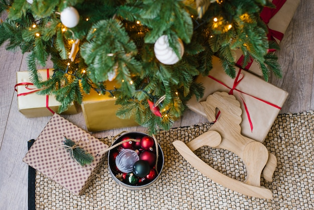 Christmas gifts, wooden rocking horse toy and christmas tree toys in box under christmas tree, top view