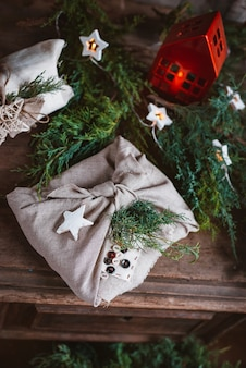 전나무와 가문비 나무의 침엽수 가지에 일본식 보자기 직물로 싸인 크리스마스 선물. 새해 휴가 준비 및 설계. 소박한 스타일의 손으로 만든, 저렴한 아이디어