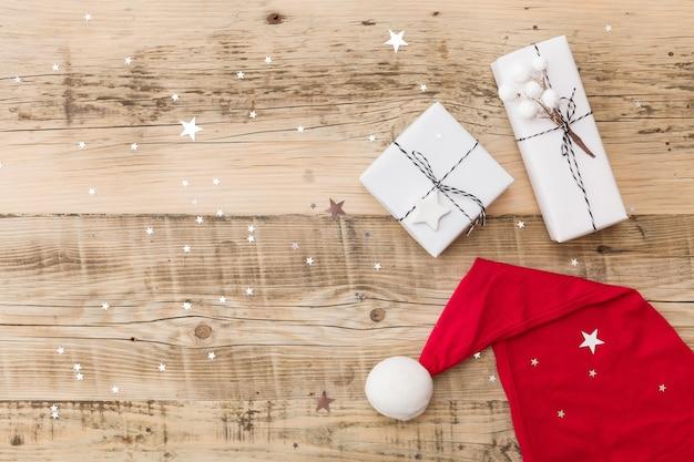 Рождественские подарки, завернутые в белую подарочную бумагу в шляпе дедов морозов на деревянном фоне со сверкающими звездами