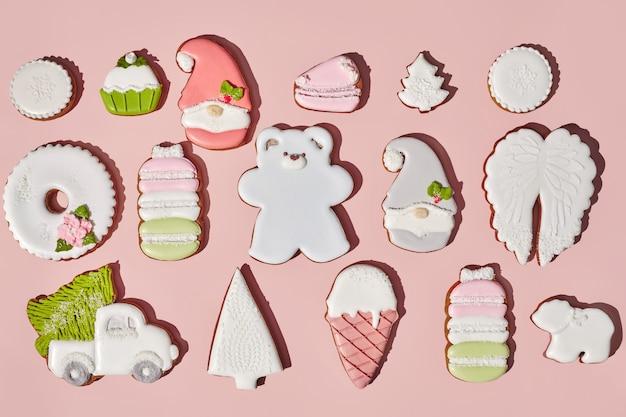 Рождественское имбирное печенье с сахарной глазурью на розовом фоне