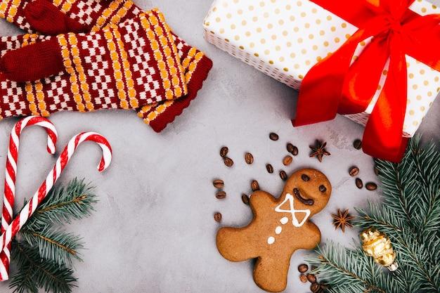 Pan di zenzero di natale, chicchi di caffè, rami di abete, guanti caldi e scatola regalo sul pavimento grigio
