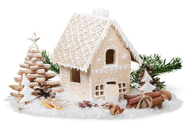 白い背景で隔離のクリスマスジンジャーブレッドクッキーハウス。