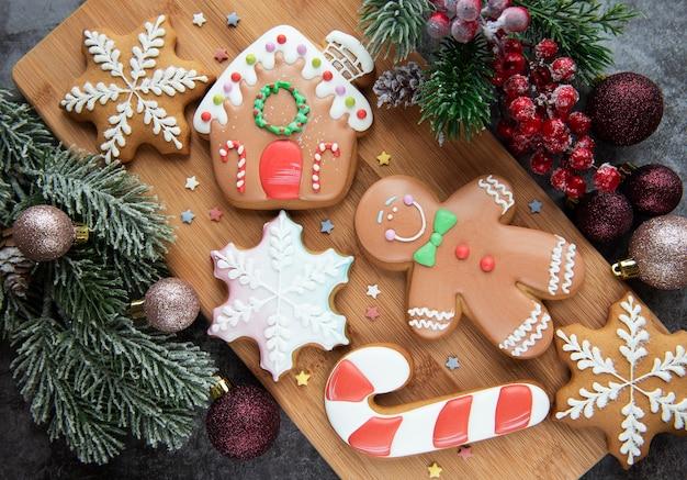 크리스마스 진저 쿠키와 크리스마스 장식입니다. 나무 배경에 집에서 만든 맛있는 크리스마스 진저.
