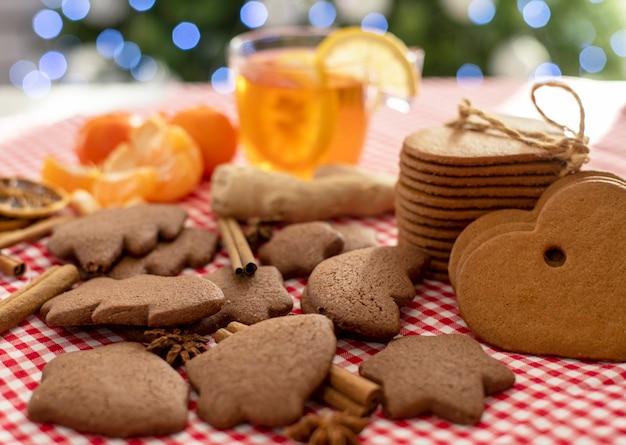 クリスマスツリーの背景に柑橘系のお茶と生姜の横にある赤い市松模様のテーブルクロスにクリスマスジンジャーブレッドクッキーとシナモン
