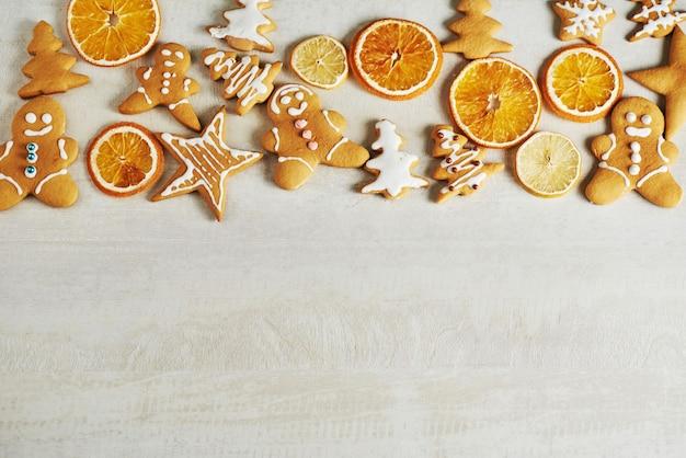 クリスマスジンジャーブレッドクッキーと乾燥したオレンジと白いテーブルの上のスパイス