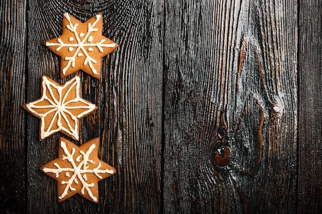 Christmas gingerbread cookies on dark wooden background