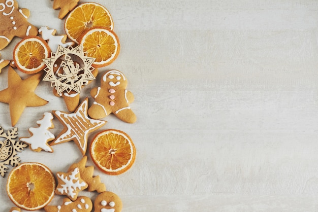 Christmas gingerbread cookies and dried orange and spices on white table