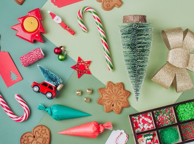 Christmas gingerbread cookies, icing bags, sprinkling and decor on green color surfaces. top view, flat lay.
