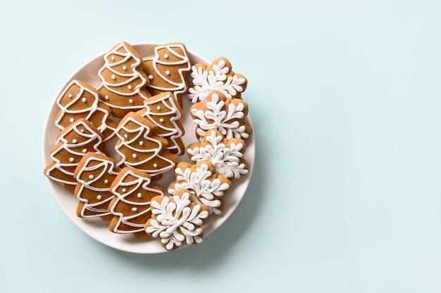 밝은 파란색 배경에 접시에 크리스마스 진저 쿠키. 복사 공간 메리 크리스마스와 새 해 복 많이 인사말 카드. 위에서 봅니다.