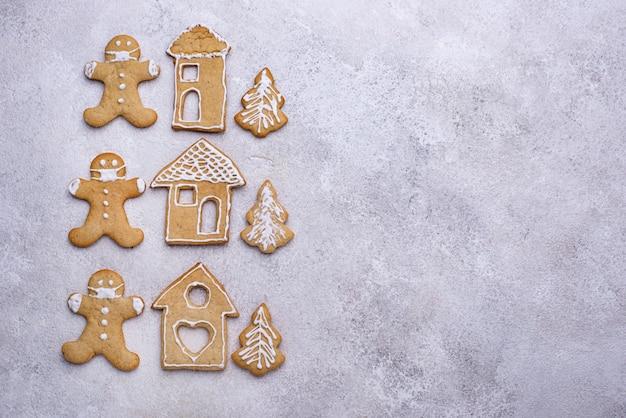 家とマスクの男の形のクリスマスジンジャーブレッドクッキー。家にいるコンセプト