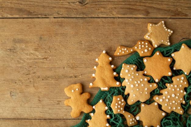 Рождественские пряники лежат в зеленой авоське на светло-коричневом деревянном